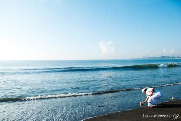 Seorang Pemangku sedang mengambil air laut untuk dijadikan Tirta