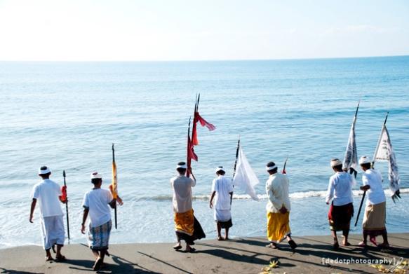 Mencelupkan beberapa sarana upacara pura ke dalam air laut